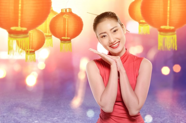 La donna cinese asiatica in un vestito dal cheongsam celebra il nuovo anno cinese