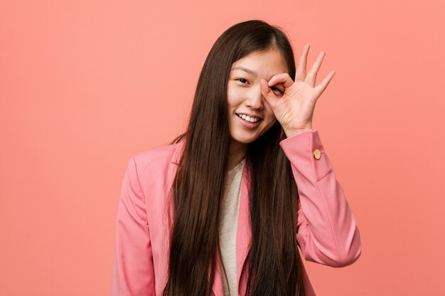 La donna cinese dei giovani affari che indossa il vestito rosa ha eccitato mantenendo il gesto giusto sull'occhio.