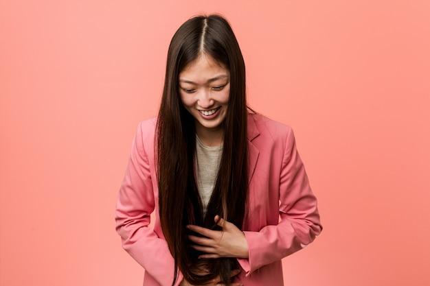 La donna cinese di giovani affari che indossa il vestito rosa ride felicemente e si diverte tenendo le mani sullo stomaco.