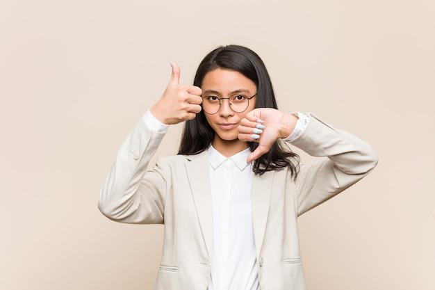 La donna cinese di giovani affari che mostra i pollici su e pollici giù, difficile sceglie il concetto