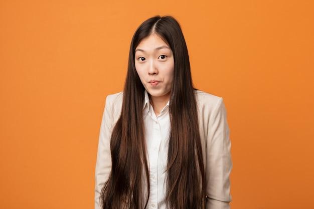 La donna cinese di giovani affari scrolla le spalle le spalle e gli occhi aperti confusi.