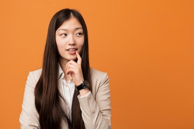 La donna cinese di giovani affari si è distesa pensando a qualcosa che esamina uno spazio della copia.