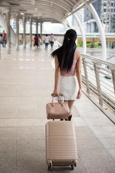 La donna cinese tira i bagagli per viaggiare