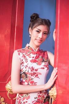 La donna cinese veste il camaleonte tradizionale al tempio cinese.