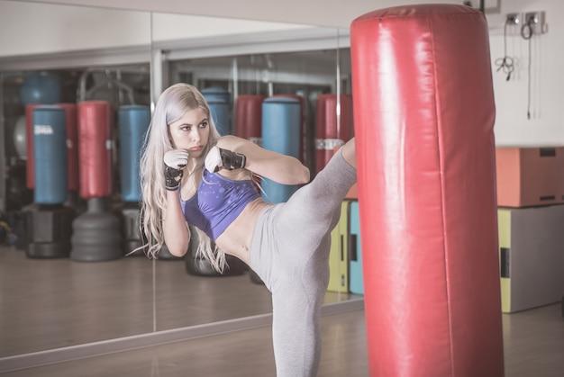 La donna combattente colpisce la borsa pesante