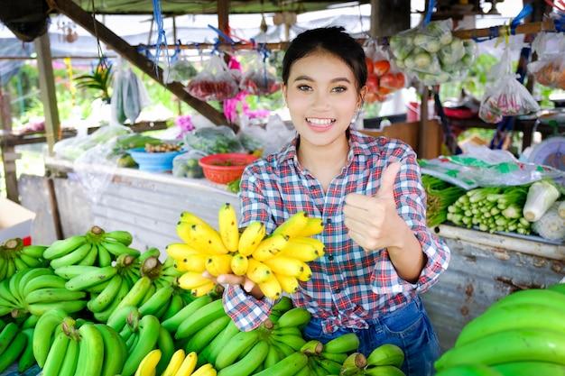 La donna commerciante vende verdura, frutta e banane gialle mature in un negozio di strada rurale