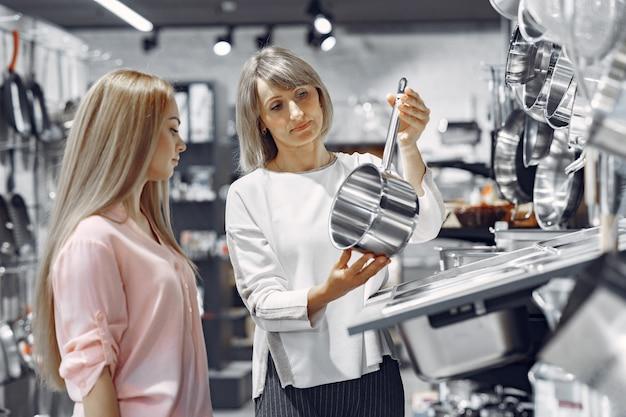 La donna compra i piatti nel negozio