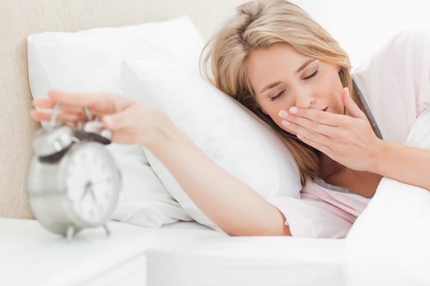 La donna con gli occhi chiusi sta raggiungendo per mettere a tacere la sua sveglia