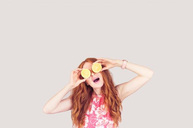 La donna con i capelli rossi tiene due limoni sugli occhi