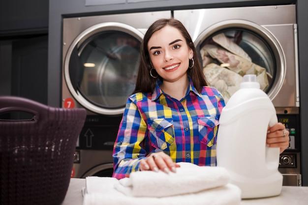 La donna con il detersivo imbottiglia la lavanderia automatica.