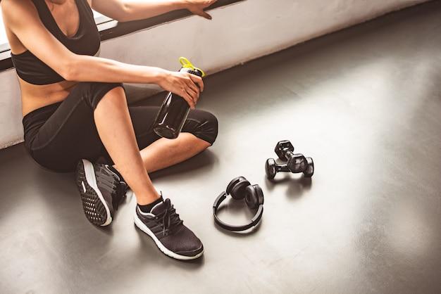 La donna con l'allenamento di stile di vita di esercizio del dumbbell e del dispositivo nella rottura di forma fisica della palestra si rilassa