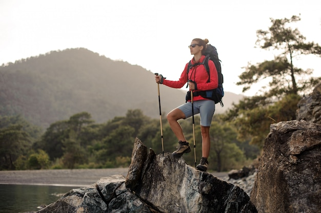 La donna con l'attrezzatura per l'escursionismo cammina attraverso la costa sassosa
