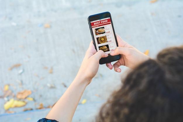 La donna con l'ordinazione dello smartphone porta via l'alimento