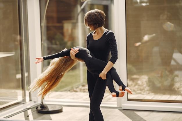 La donna con la figlia è impegnata in ginnastica