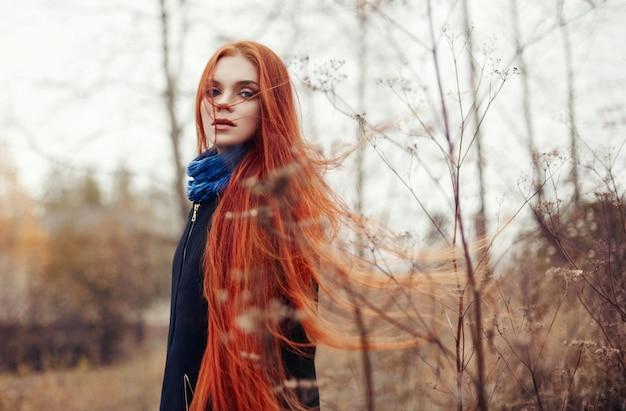 La donna con lunghi capelli rossi cammina in autunno sulla strada