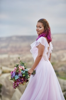 La donna con un bel mazzo di fiori nelle sue mani si erge sulla montagna sotto i raggi del tramonto all'alba