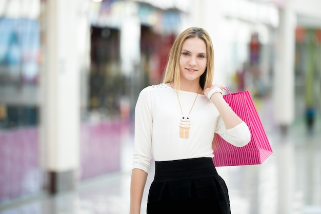 La donna con un sacchetto di acquisto di colore rosa