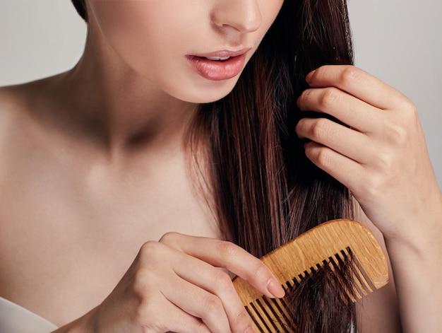La donna con un umore giocoso si pettina i capelli con un pettine marrone chiaro con la mano destra sul, tiene i capelli con la mano sinistra