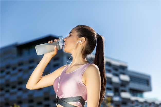 La donna con una coda di cavallo sta bevendo dalla bottiglia sportiva nelle cuffie vicino all'edificio moderno