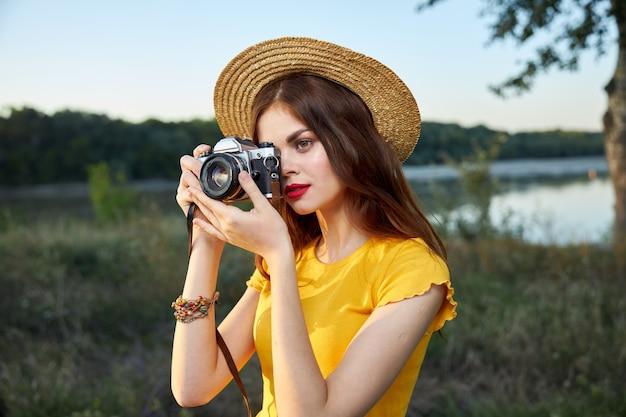 La donna con una macchina fotografica esamina il viaggio dell'aria fresca della natura dell'obiettivo della fotocamera