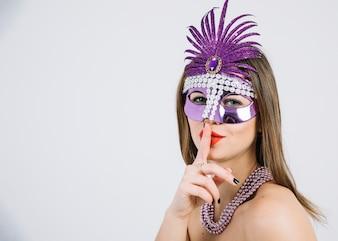 La donna con una mascherina di carnevale che fa il silenzio gesture su fondo bianco