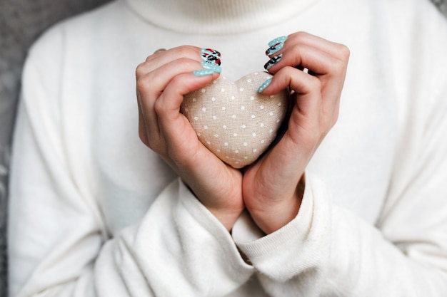 La donna con una pietra a forma di cuore in mano