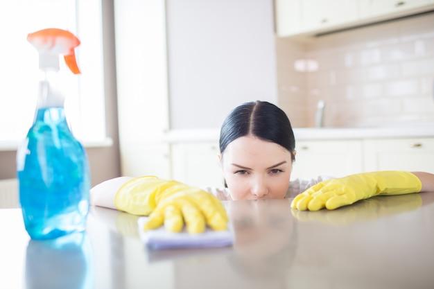 La donna concentrata sta pulendo la superficie di sguardo della tabella con lo straccio. spray blu si trova sul tavolo. indossa guanti gialli.