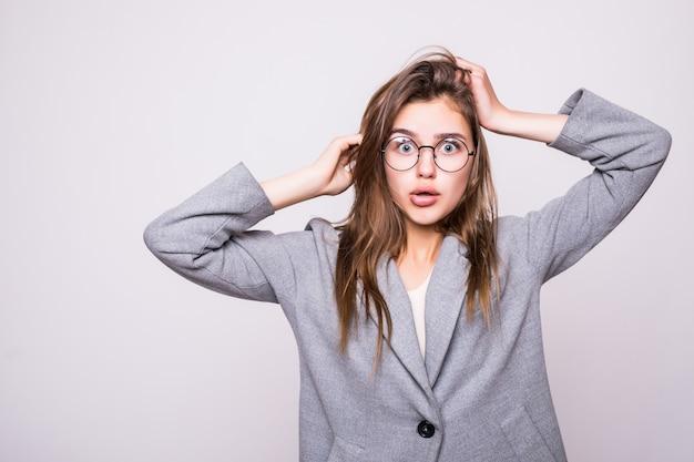 La donna confusa mette le sue mani sulla testa, isolata su fondo bianco