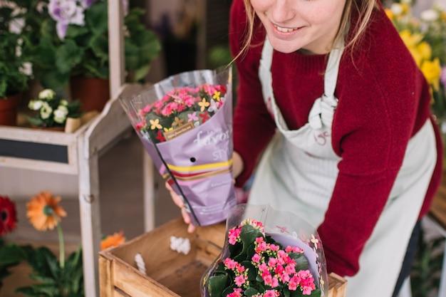 La donna contenta che organizza i fiori consegnati