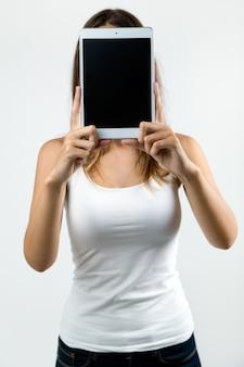 La donna copre il suo volto con la tavoletta digitale. isolato su bianco.