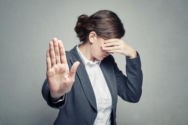 La donna copre il viso e mostra il gesto di stop