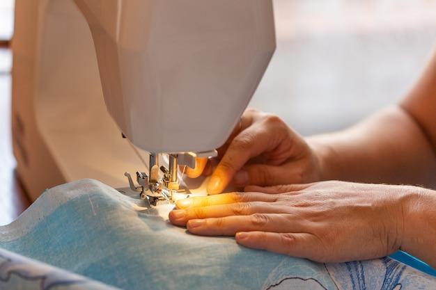 La donna cuce su una macchina da cucire