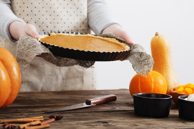 La donna cucina la torta di zucca su bianco