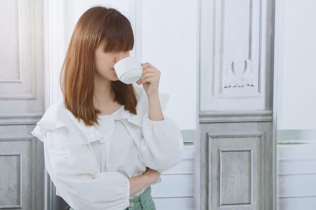 La donna d'affari asiatica si è goduta il momento di relax e ha bevuto una tazza di caffè aromatico a casa. femmina con tazza di caffè.