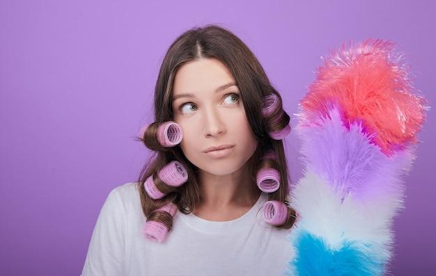 La donna dai capelli castani sveglia in bigodini tiene una spazzola per la polvere.