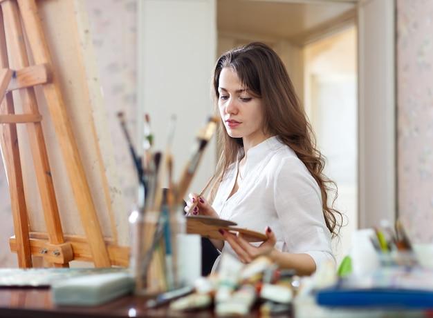 La donna dai capelli lunghi dipinge su tela