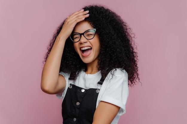 La donna dai capelli ricci soddisfatta felicissima tiene la mano sulla fronte