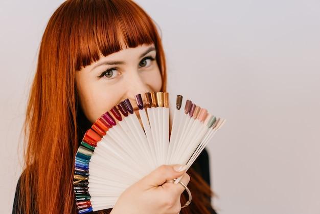La donna dai capelli rossi tiene in mano campioni di una vernice gel sotto forma di semicerchio su bianco.
