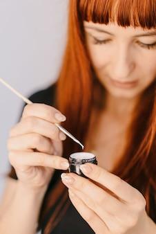 La donna dai capelli rossi tiene un pennello con un barattolo e guarda la trama di gel-lacca.