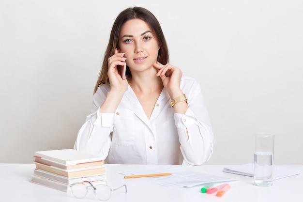 La donna dai capelli scuri dall'aspetto piacevole ha una conversazione tramite telefono cellulare, coinvolta nel processo di lavoro, scrive alcune informazioni, studia la documentazione, isolata sul muro bianco. concetto di tecnologia