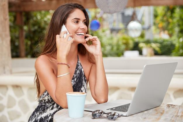 La donna dall'aspetto piacevole ha un'espressione allegra mentre parla tramite smartphone, lavora su un computer portatile, beve caffè al bar, ama la comunicazione online. persone, stile di vita, concetto di conversazione