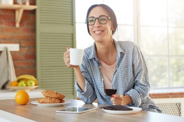 La donna dall'aspetto piacevole indossa una camicia casual e occhiali alla moda, tiene la tazza con il caffè e mangia cioccolato dolce,