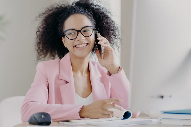 La donna dalla pelle scura dai capelli abbastanza ricci gode di una conversazione telefonica con un collega