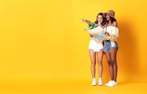 La donna degli amici si è vestita in vestiti di estate che tengono la guida della mappa di viaggio e la mano rivolta verso l'alto per copiare lo spazio