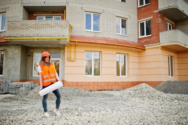 La donna del costruttore dell'ingegnere in panciotto uniforme e casco protettivo arancio tiene il rotolo della carta da disegno di affari contro la nuova costruzione