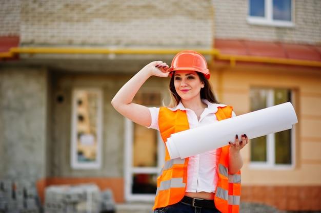 La donna del costruttore dell'ingegnere in panciotto uniforme e casco protettivo arancio tiene le carte d'ufficio contro la nuova costruzione