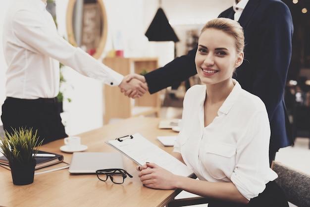 La donna del direttore delle risorse umane in camicetta e gonna sta lavorando in ufficio.
