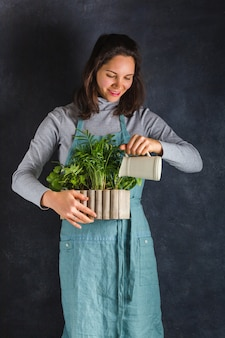 La donna del giardiniere tiene una scatola di legno con le piante in mano e annaffiata da un decanter