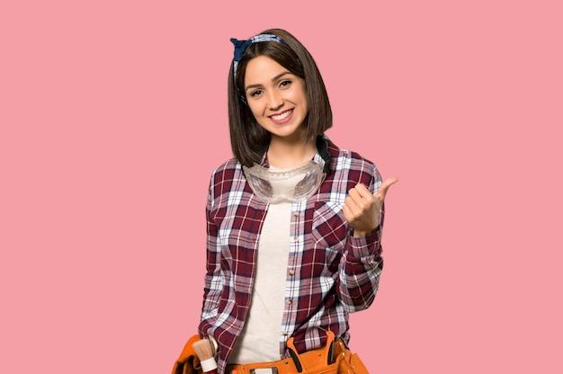 La donna del giovane operaio che dà un pollice aumenta il gesto e che sorride sulla parete rosa isolata