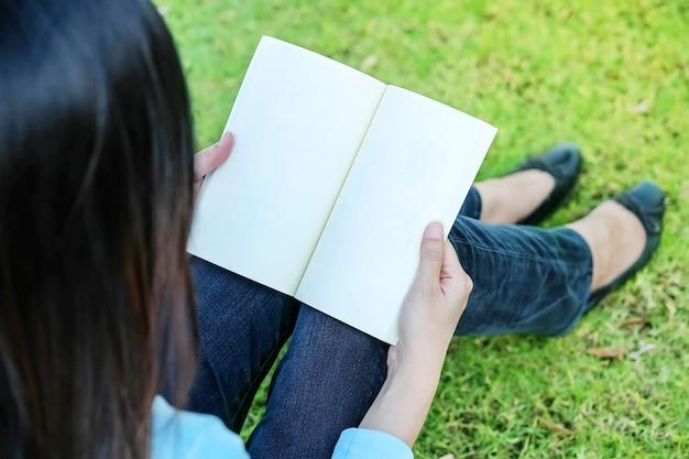 La donna del primo piano che si siede per la lettura del libro nel tempo libero sul pavimento dell'erba nel giardino dentro si rilassa il tempo del concetto asiatico della donna